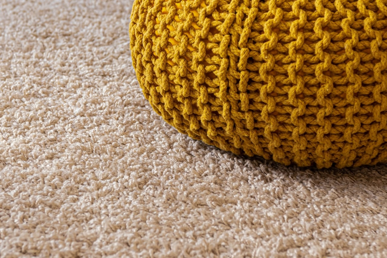Yellow knitted bag on carpet